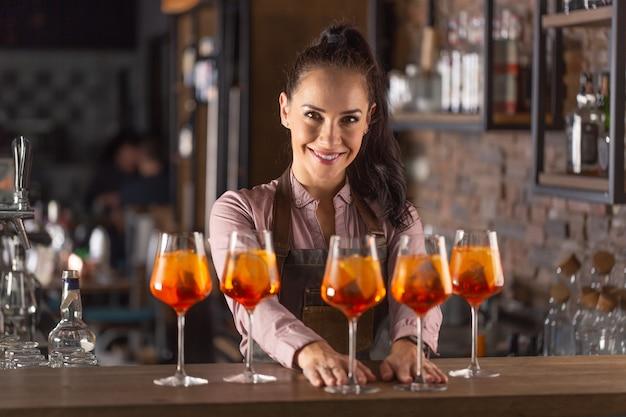 O belo barman serve cinco coquetéis de laranja em taças de vinho em um bar.