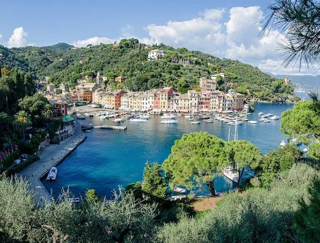 O belo panorama de portofino com casas coloridas, barcos e iate em little bay harbor. ligúria, itália