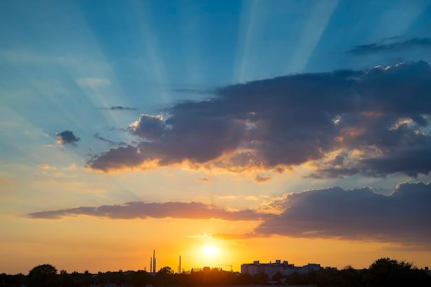 O belo pôr do sol sobre as árvores e pôr do sol do céu de ouro com luz solar natural contra