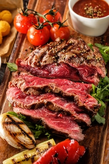 O bife de lombo grelhado fatiado raro médio suculento serviu com tomates e bolas de queijo em uma placa de madeira velha.