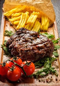 O bife de lombo grelhado saboroso suculento serviu com tomates e batatas fritas em uma placa de madeira velha.