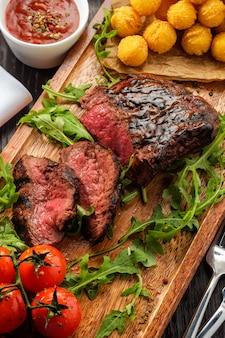 O bife de lombo grelhado saboroso suculento serviu com tomates e bolas de queijo em uma placa de madeira velha.