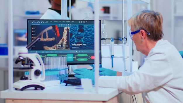 O bioquímico woaman sênior verifica as manifestações do vírus, trabalhando em um laboratório moderno e equipado. equipe de médicos examinando a evolução da vacina usando diagnóstico de pesquisa de alta tecnologia contra covid19