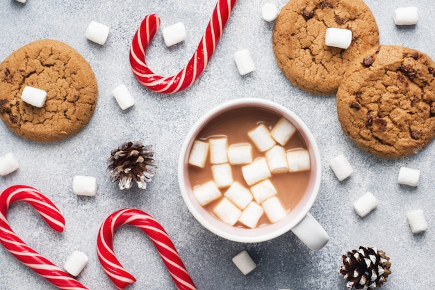 O biscoito de chocolate, caramelo de natal, copo de chocolate e cones de marshmallow decorações em um cinza. fechar-se