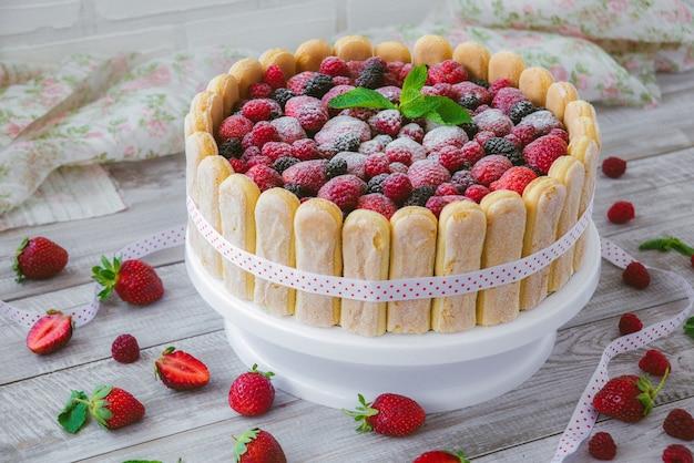 O biscoito de verão nua barganhando com creme de mascarpone e frutas frescas em uma superfície de madeira Foto Premium