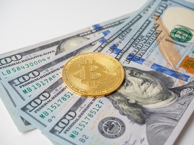O bitcoin amarelo encontra-se em notas de cem dólares. o conceito de criptomoeda, investimento, renda