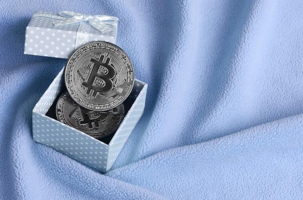 O bitcoin de prata encontra-se em uma pequena caixa de presente azul com um pequeno arco