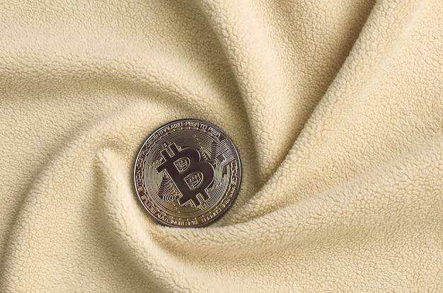 O bitcoin dourado encontra-se em um cobertor feito de tecido de lã laranja claro macio e fofo