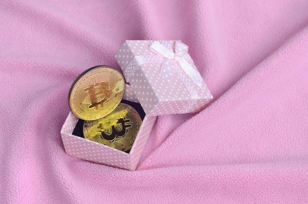 O bitcoin dourado encontra-se em uma pequena caixa de presente rosa com um pequeno laço em um cobertor
