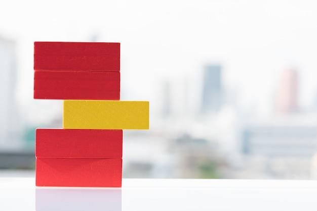 O bloco amarelo entre blocos de madeira vermelhos brinca com fundos da cidade e do céu.