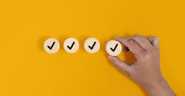 O bloco circular de madeira é colocado sobre um fundo amarelo e com uma marca de seleção, a mão está pegando o bloco de madeira. conceito de bloco de madeira, banner com espaço de cópia para texto, cartaz, modelo de maquete.