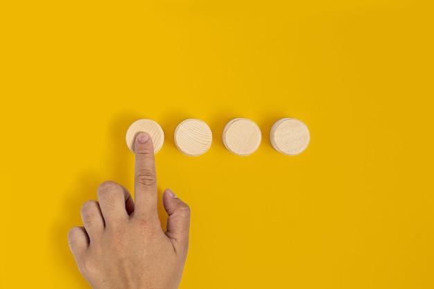 O bloco de madeira circular é colocado sobre um fundo amarelo e os gestos com as mãos pressionam o bloco de madeira da mesma forma que pressionar um botão. banner com espaço de cópia para texto, cartaz, modelo de maquete.