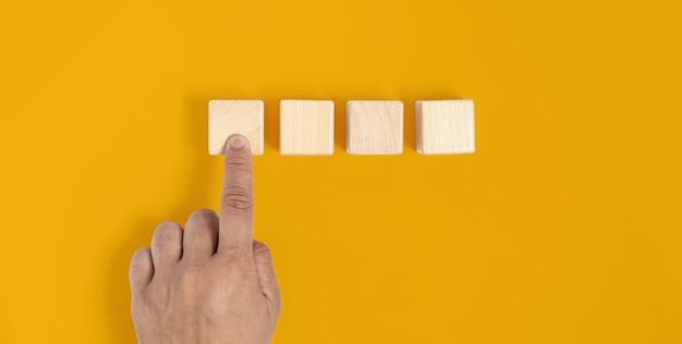 O bloco de madeira quadrado é colocado sobre um fundo amarelo, pressionado à mão no primeiro bloco de madeira semelhante a pressionar um botão. conceito de bloco de madeira, banner com espaço de cópia para texto, cartaz, modelo de maquete.