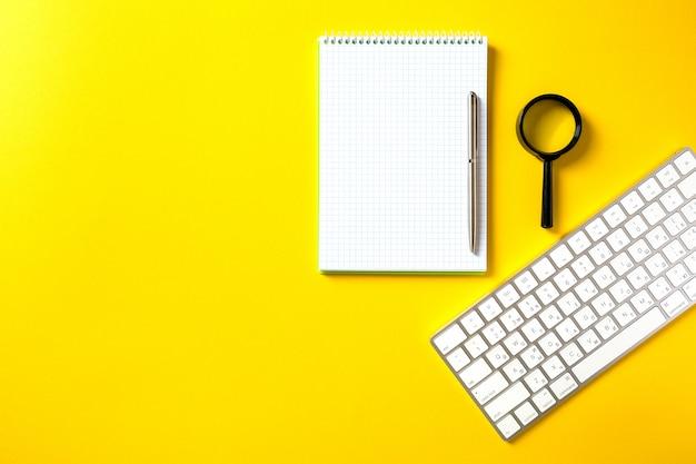 O bloco de notas aberto branco e teclado de computador isolado em amarelo