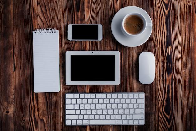 O bloco de notas aberto branco e teclado de computador isolado no desktop de madeira