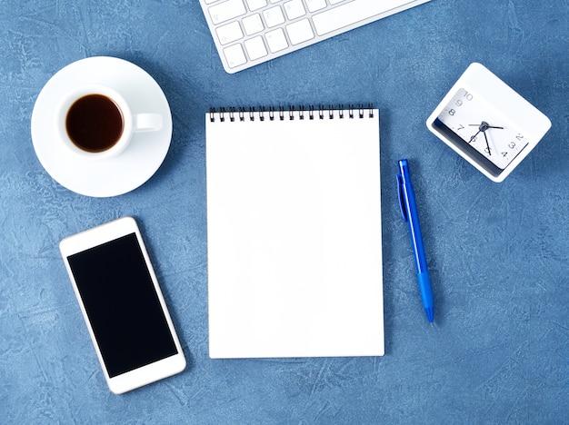 O bloco de notas aberto com a página branca limpa, copo de café na tabela azul, vista superior.