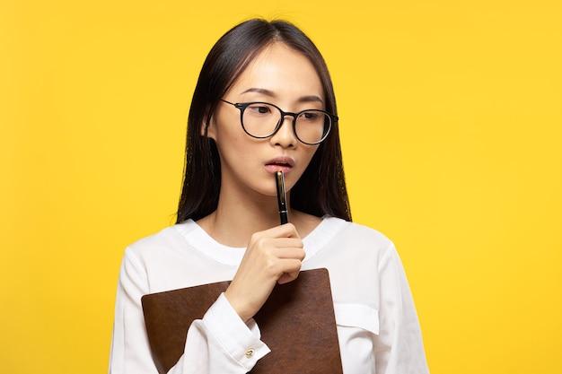 O bloco de notas de aparência asiática de mulher nas mãos trabalha amarelo.