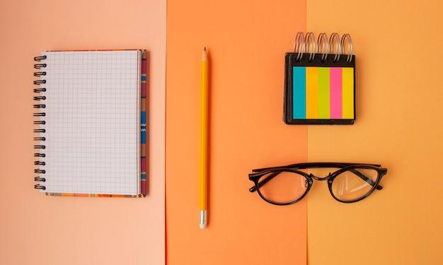 O bloco de notas de volta às aulas na vista superior dos óculos xadrez