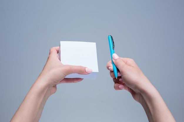 O bloco de notas e a caneta em mãos femininas