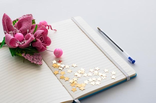 O bloco de notas em branco com o ramalhete de flores da mola e vislumbra estrelas.