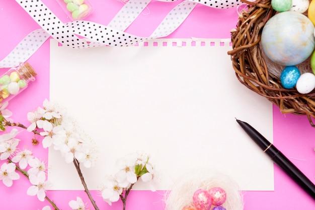 O bloco de notas em branco e a folha de rucca com elementos decorativos de páscoa.