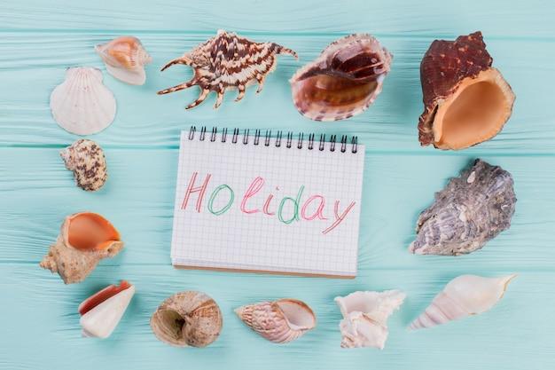O bloco de notas está rodeado por conchas no fundo turquesa
