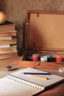 O bloco de notas está sobre a mesa com tintas