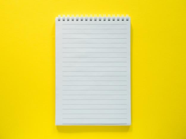 O bloco de notas para escrever no desktop amarelo, horizontalmente leigos, copia o espaço.