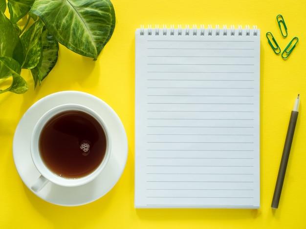 O bloco de notas para notas, folhas verdes planta o copo de café no desktop amarelo, configuração lisa, espaço da cópia.
