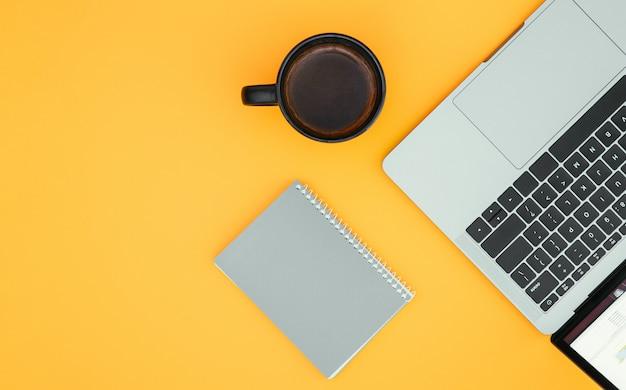 O bloco de notas, uma xícara de café e um laptop são isolados em uma superfície laranja e um local para o texto. copyspace
