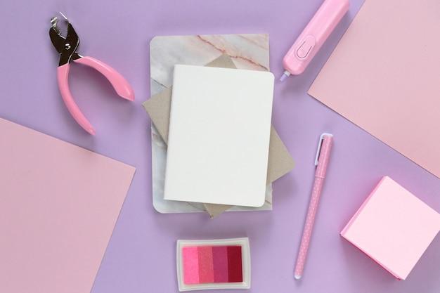O bloco de notas vazio com artigos de papelaria em tons pastel na moda.