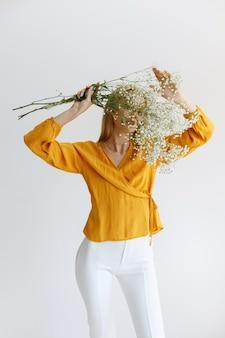 O blogger com flores cobre o rosto em um fundo monocromático