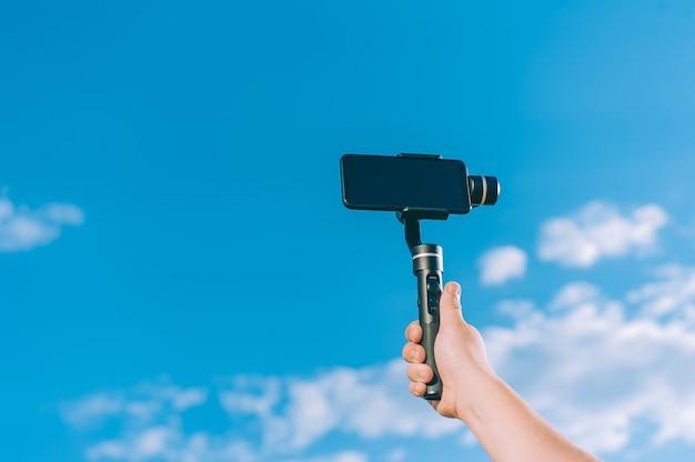 O blogger está gravando vídeos em um smartphone com um gimbal portátil contra um céu com nuvens.
