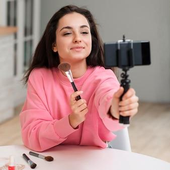 O blogger mostrando seus pincéis de maquiagem e gravando