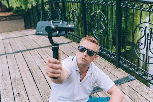 O blogger na natureza grava vídeo em um smartphone