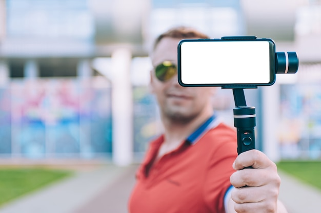 O blogger no estádio grava vídeo em um smartphone com um estabilizador de câmera manual.