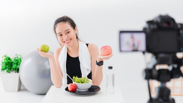 O blogger saudável da mulher asiática bonita está mostrando o fruite da maçã e limpa o alimento da dieta.