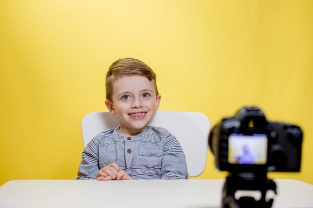 O blogueiro infantil grava seu vlog em casa. menino gravando seu videoblog. o pequeno vlogger faz streaming online usando a câmera.