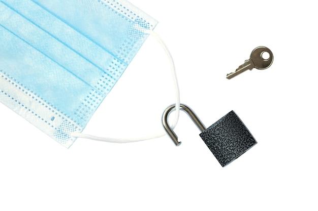 O bloqueio acabou máscara médica com um cadeado desbloqueado e uma chave isolada no fundo branco