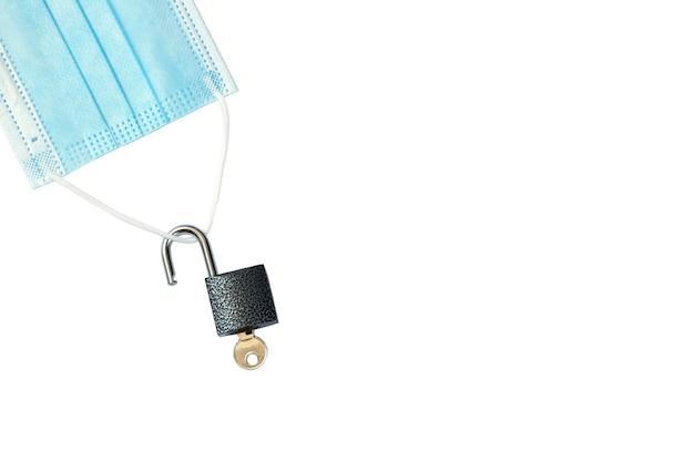 O bloqueio acabou máscara médica com um cadeado desbloqueado isolado no fundo branco copie o espaço