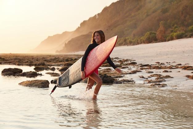 O bodysurfer feliz tem um sorriso agradável e amigável, parece positivamente de lado, tem pernas delgadas, pele bronzeada