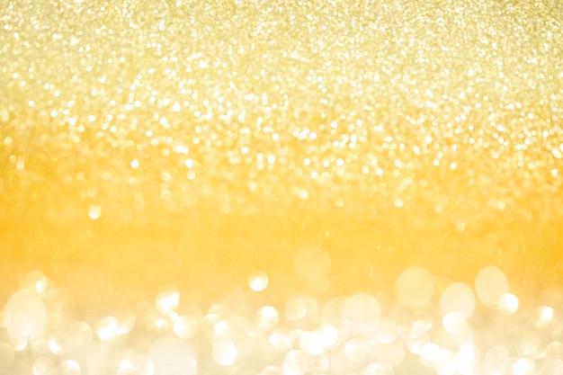 O bokeh abstrato do brilho do ouro ilumina-se com fundo da luz suave.