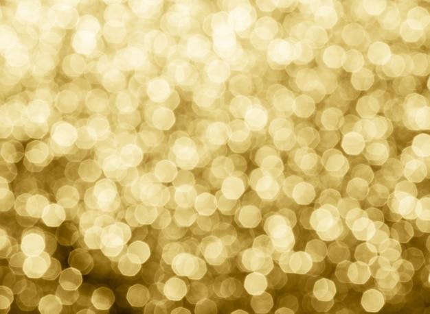 O bokeh abstrato do ouro circunda para o fundo do natal. bokeh luz de fundo.