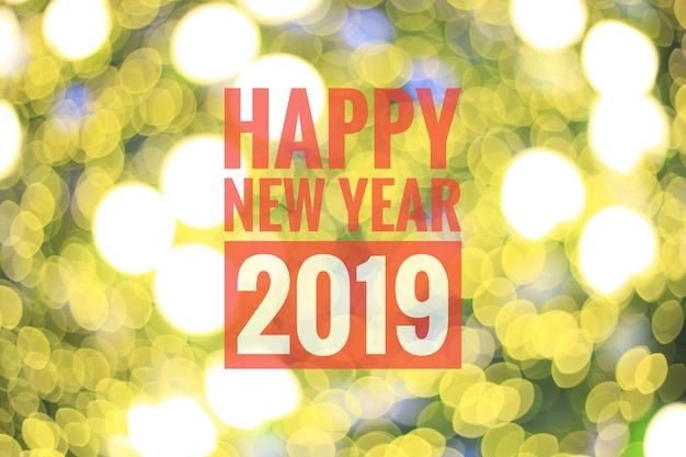O bokeh amarelo borrado ilumina-se como o fundo, com ano novo feliz 2019 do texto da cor vermelha.