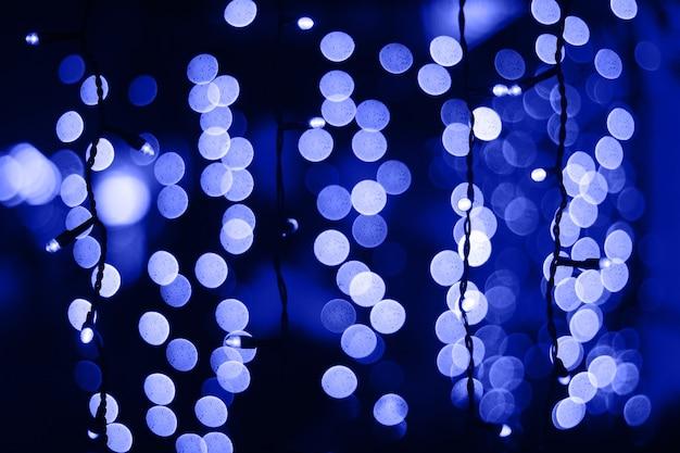 O bokeh azul clássico abstrato desfocado ilumina o fundo garland em primeiro plano