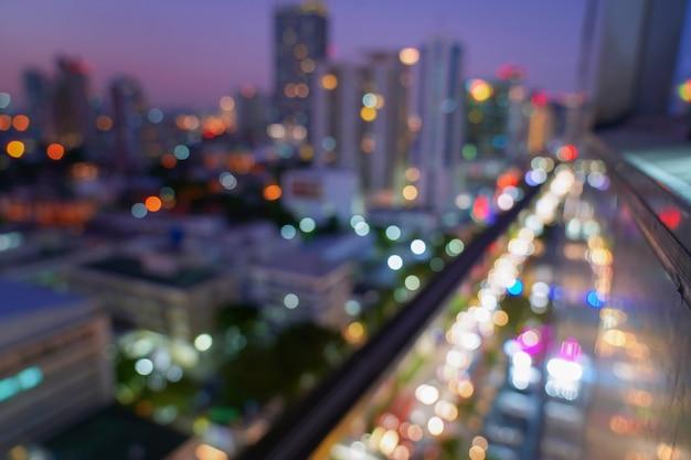 O bokeh claro da luz do carro no fundo preto, nivelando o tráfego na cidade ilumina o borrão de movimento.