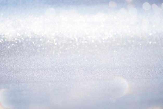 O bokeh de prata abstrato do brilho ilumina-se com fundo da luz suave.