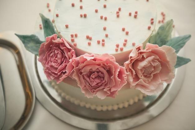 O bolo de casamento é decorado com flores cor de rosa.