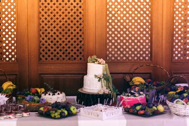 O bolo de casamento e o carrinho de doces servidos no bloco no buffet