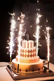O bolo de casamento festivo com fogos de artifício em um fundo escuro